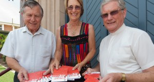 Frank Millett, Heather Donald and Rev Ray Nutley use Uniting Communications' Christmas postcards to spread the news about the Bundaberg Uniting Church Christmas services.