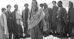Enrique Irazoqui (centre) stars in Pasolini's The Gospel According to Matthew. A photo of men in robes is shown. Photo property of Eureka Entertainment Limited.