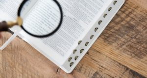 Magnifying glass over an open Bible.