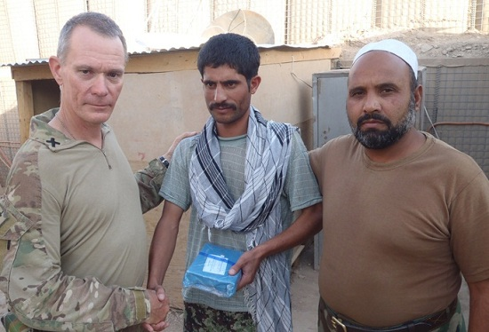 Army chaplain Rev John Saunders presents a copy of the Qur'an to a village mullah in Afghanistan. Photo: John Saunders