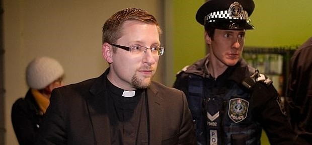 Reverend John Hughes, of Brougham Place Uniting Church, is arrested for trespassing at the Mt Barker electoral office of Federal MP Jamie Briggs after staging a sit-in to protest children being held in immigration detention centres.