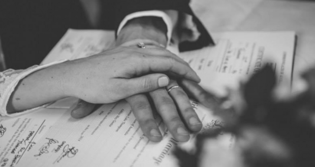 A couple's hand over newly signed marriage papers. Photo by Kait Barker.