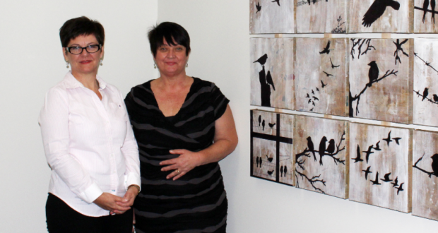 Jo Munday (left) and Adriana Leonardi (right) pictured with a piece of art made out of recycled newspapers by Cooinda mental health participants—to be displayed at the upcoming exhibition. Photo by UnitingCare Health.