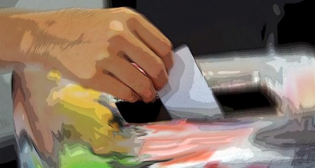 A hand casting a ballot