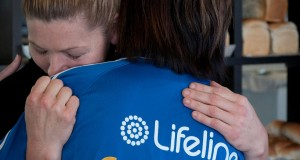A Lifeline representative hugging a member of the public. Photo by UnitingCare.