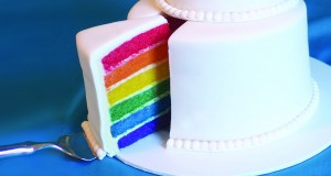 A traditional wedding cake with a rainbow layered sponge. Photo by Holly Jewell.