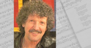 Photo of singer/songwriter Robin Mann with music sheets.