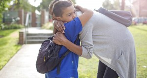 Young school boy hugging this mother goodbye. Photo: iStock