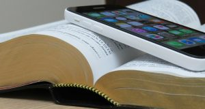 Photo of an iPhone on top of a Bible.