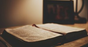 Photo of a Bible open on a bedside table with a blurred out family photo.